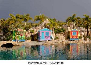3 colourful beach houses near a lagoon.