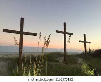 3 crosses on the beach at sunset