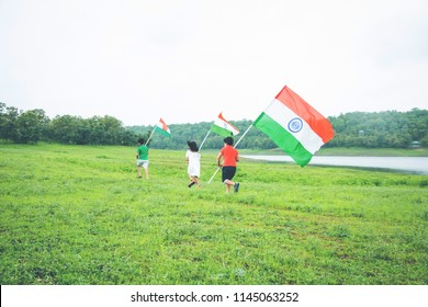 3 cute little indian kids holding, waving or running with Tricolour near a lake with greenery in the background, celebrating Independence or Republic day