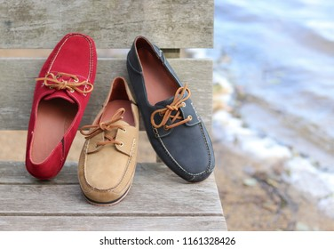 3 different colors of men's boat shoes made from real leather, taken by the water at the ocean. These casual and formal footwear accessories are colorful and fashionable.