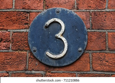 3 Digit on Dark Metal Background on red brick wall. Number three