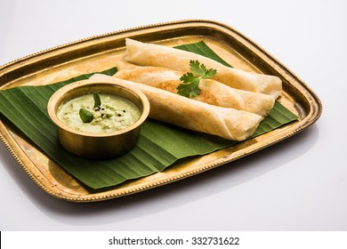3 dosa rolls with coconut chutney in a brass tray over coconut leaf, favourite south indian meal,white background