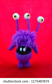 3 eyed purple monster amigurumi crochet toy, vivid red background.