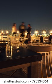 3 friends standing on a chic rooftop bar at night in Manhattan. Stools and table, large string lights along the balcony, lights of New York City in the background. Low light photography, motion blur.