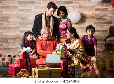 3 generations of Indian family celebrating Diwali festival or birthday by exchanging gifts and sweets while sitting on Sofa, Indoors