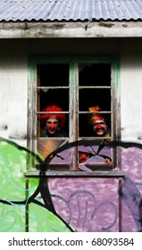 3 Ghoulish Clowns Stare Peering Out Of The Darkness Inside The Haunted House Of Horrors