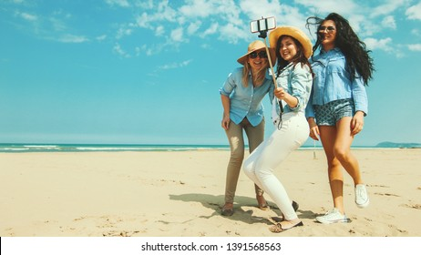 3 girls on beach vacation. happy friends on a sunny beach with blue sky in background  taking a selfie photo wearing casual clothes and sunglasses.