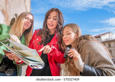 3 girls on holiday, reading map. group of young friends or university students on excursion  or sightseeing trip on a tourist destination looking for directions