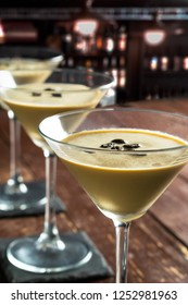 3 Glasses of Espresso Martini Cocktail, vodka, kahlua, espresso coffee, in a Martini glass on wooden table. Vertical image