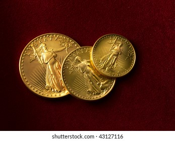 3 gold liberty coins shot on red suade