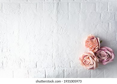 3 heads of vintage roses on white brick cracked background with blur