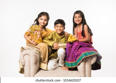 3 indian kids or siblings in traditional wear sitting on sofa or white background, holding gifts and sweets or laddu