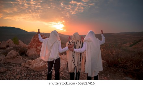 3 Jewish men prayer With  Talit and tefillin in sunset