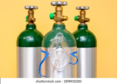 3 Medical Oxygen Tanks with Oxygen Mask on One of Them