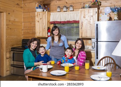 3 Mexican sisters with their children at a table in the kitchen