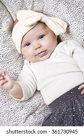 3 month old baby lying down wearing a skirt and a bow in her hair