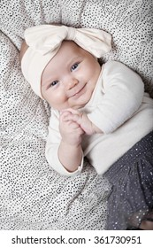 3 month old baby lying down wearing a bow, laughing and holding hands