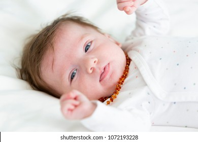 3 month old  beautiful, cute baby with amber necklace