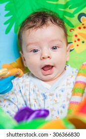 3 months old baby boy playing and learning on the playmat.