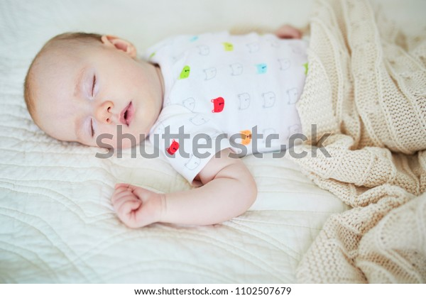 3 months old baby girl sleeping under knitted blanket. Child having a day nap in parents' bed