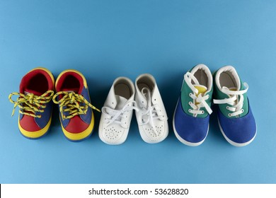 3 pair of baby shoes lined up on blue background with space for copy