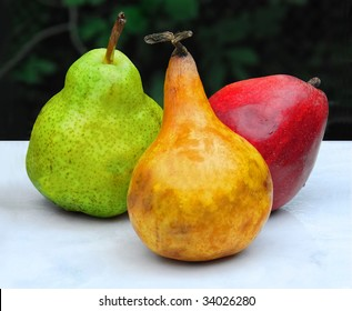 3 Pears: Artistic still life with three varieties of pear. Red yellow and green on a white surface against a dark background.