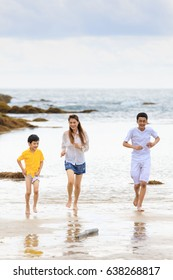 3 people Asian family, mother and 2 sons playing running and learning for new experience on sand beach of tropical sea with funny and happiness manner