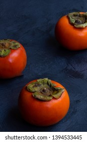 3 persimmons from 45 degrees on grey textured background