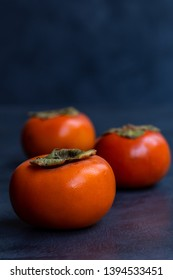 3 persimmons in a row vertical orientation on grey textured background