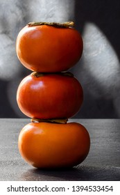 3 persimmons stacked one on top of the other on grey textured background in hard light with shadows