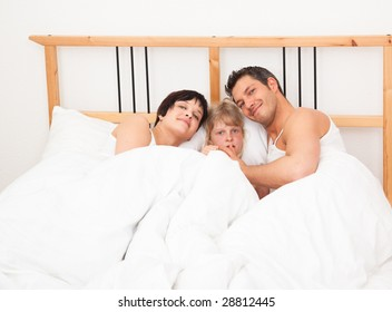 3 persons lying together bedtime