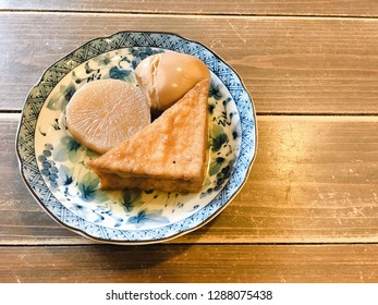 3 pieces of Oden ingredients consisting of egg, white radish and fish paste, on a small blue plate. Oden is a Japanese one-pot dish consisting of several ingredients in soy-flavored dashi broth.