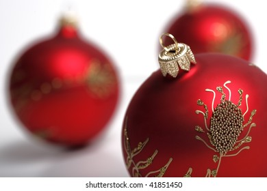 3 red christmas decoration balls on a white background. Focus on a foreground ball. Shallow DOF.