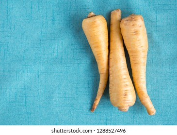 3 ripe parsnips on a turquoise linen cloth with copy space