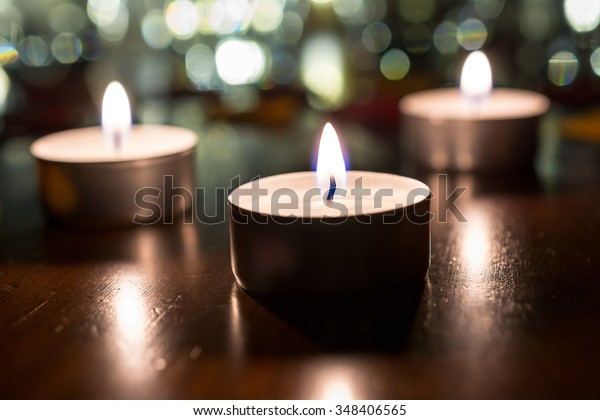 3 Romantic Tea Lights For Dinner On Wooden Table With Bokeh At Night