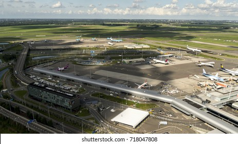 3 September 2017, Amsterdam, Holland. Aerial view of gate M on Schiphol Airport. A clear horizon, blue sky with cumulus and a cloud shadow over the field. Jetplanes are from WOW, TUI, Easyjet and KLM.