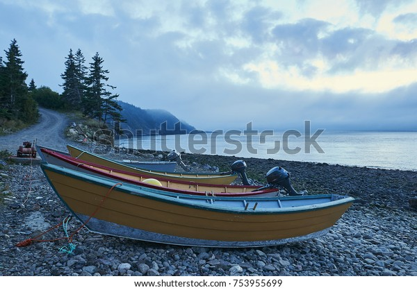 3 small fishing boats on shore late evening