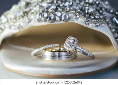 3 stacked wedding rings inside brides wedding shoe.