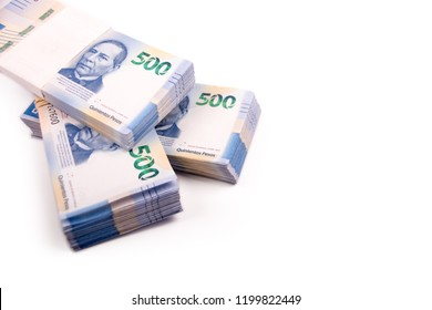 3 stacks of 500 Mexican pesos bills, new design of bills on white background