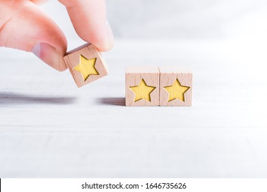 3 Star Ranking Formed By Wooden Blocks And Arranged By A Male Finger On A White Table