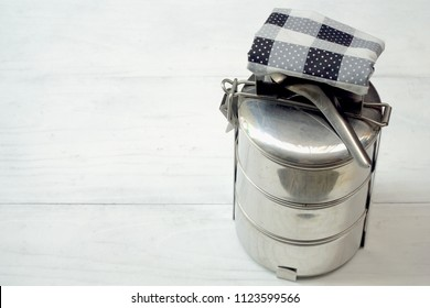 3 step of Antique stainless steel food carrier (Tiffin food container) and spoon on wood background. Vintage. Still life food. Simple style. Copy space.
