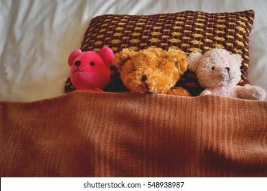 3 teddy bears sleep on bed Putting blanket on