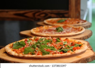 3 thin crispy traditional pizzas on wooden boards. Rocket salsa in front, Parma ham behind. Soft focus