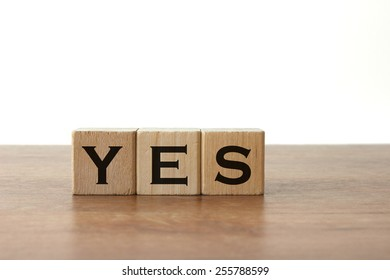 "3 Toy Wood Blocks With Letters: ""YES"" On a Wooden Table With Light Grey Background"