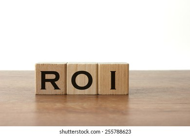 "3 Toy Wood Blocks With Letters: ""ROI"" On a Wooden Table With Light Grey Background"