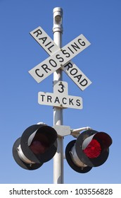 3 tracks railroad crossing sign with blinking red lights