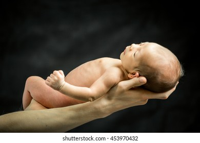 A 3 weeks old baby son laying on his father's hand