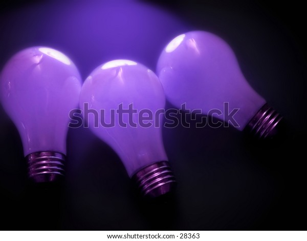 3 white, matte light bulbs in a dark environment. Purple tones, soft focus.