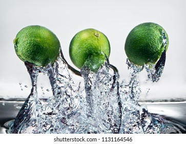 3 whole limes splash through water in high speed photograph.