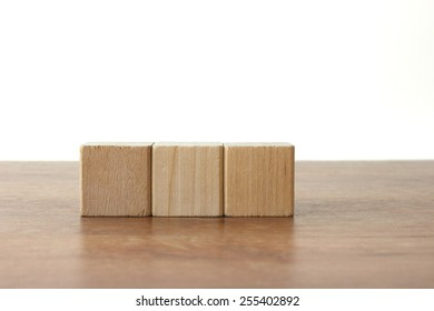 3 Wood Blocks Front View, On Wooden Table, Light-Grey Background